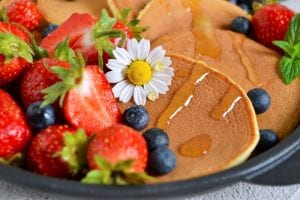 Pancakes with fruit, syrup, and a daisy