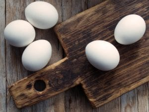 Five eggs on a wooden cutting board and table