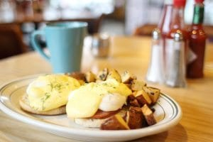 Eggs Benedict with potatoes on a wooden table