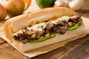 Philly Cheesesteak with green peppers on a wooden table