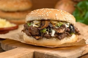 Steak and mushroom melt on a paper wrapper and wooden cutting board