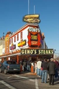 Geno's Steaks with a long line in front of it