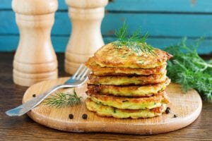 Zucchini pancakes stacked on a cutting board with garnishes