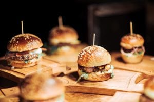 Tasty burgers on wooden trays in bar made with steam shell technology