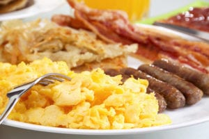 Breakfast of eggs, sausage, bacon, and hashbrowns