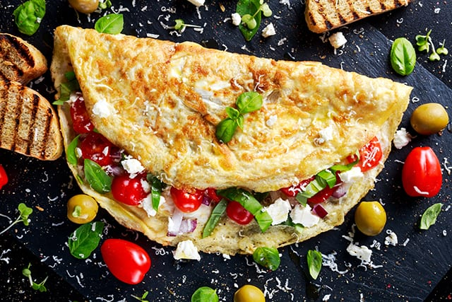 Vegetable Omelette with tomatoes, basil, greek cheese, parmesan, olives, toast.