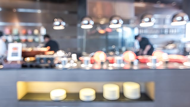 Buffet at hotel restaurant interior blur background with blurry open kitchen counter bar of food catering service business with chef staff cooking for breakfast, lunch or dinner meal