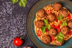 Roasted meatballs with spaghetti in a plate on a table