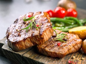 Grilled beef steaks made with commercial griddle with vegetables on a wooden cutting board