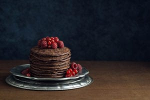 A tall stack of dark chocolate pancakes topped with fresh raspberries and red currants on a metal dish. The pancakes are on a wooden table top in front a dark blue wall. There is copy space for text in the background.