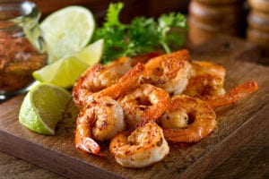 Cajun shrimp cooked on an industrial steam griddle with lime on a wooden platter