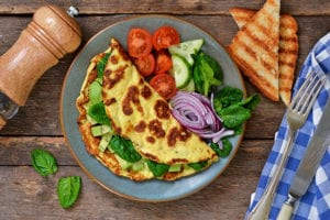 Omelette with avocado, spinach and vegetables with crispy toast from bread. Morning breakfast.