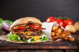 Tasty burger and french fries on wooden table