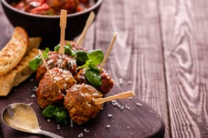 Delicious homemade meat balls with tomato sauce on skewers. Copyspace