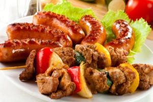 Barbecue on skewers sausage vegetables greens salad on a plate white background
