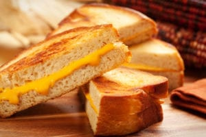 Grilled cheese on a wooden table with Indian corn in the background
