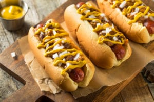 Three chili dogs with mustard and toppings