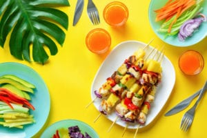 Hawaiian chicken grilled kabob on a yellow table with a variety of vegetables