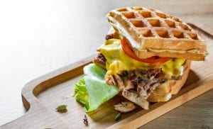 Monte Cristo waffle sandwich with meat, cheese, sauce and vegetables on wooden table background