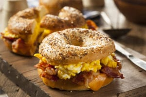 Sesame seed bagel sandwich with bacon, eggs, and cheese on a wooden cutting board