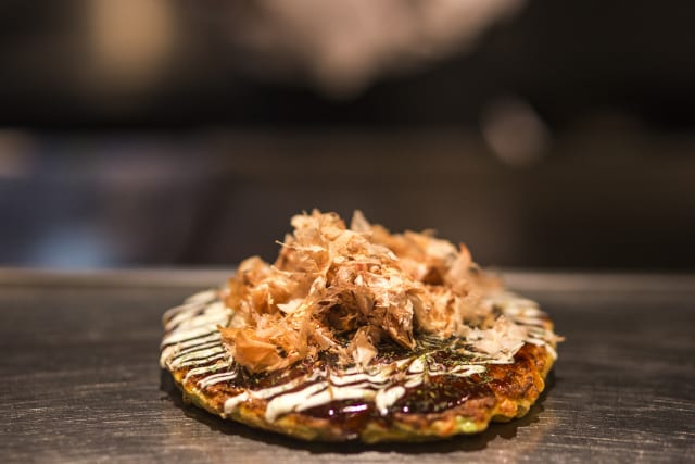 Okonomiyaki on a stem griddle topped with dark and light sauce with light shavings on top