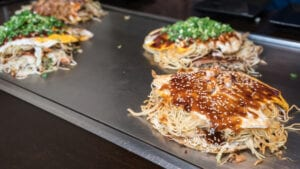 Okonomiyaki with egg on top and green onions on an American Griddle