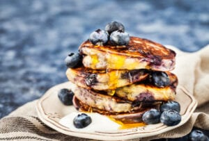 Stack of four griddle pancakes with syrup and blueberries