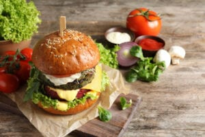 Board with vegan burger and vegetables on wooden table. Space for text