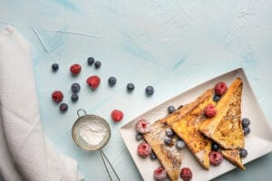 Three pieces of french toast with powdered sugar, blueberries, and rasberries
