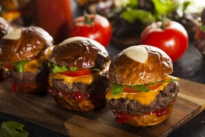 Three slider burgers with tomatoes in the background